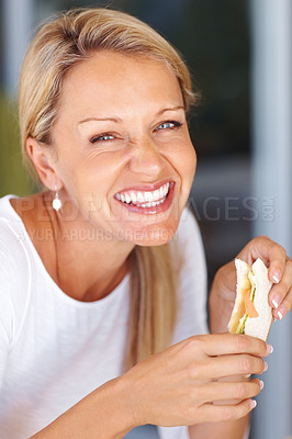 Buy stock photo Closeup portrait of a happy beautiful mature woman eating sandwich