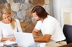 Mature couple doing home finance at dining table , using laptop