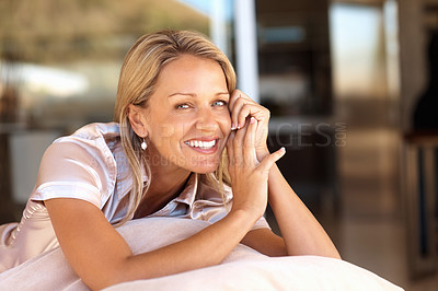 Buy stock photo Portrait of a beautiful relaxed mature woman smiling against blur background