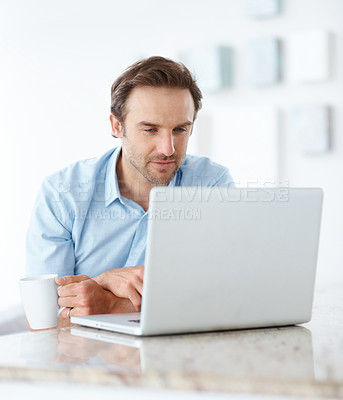 Buy stock photo Portrait of a handsome young man holding a cup of coffee and using a laptop - Indoor