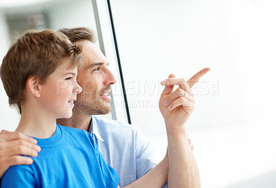 Buy stock photo Portrait of a handsome young man showing something to his son - Copyspace