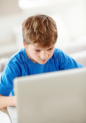 Buy stock photo Portrait of an angry little boy in front of a laptop - Indoor