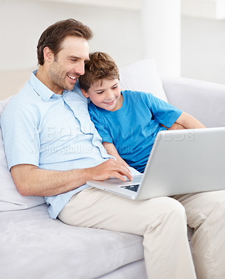 Buy stock photo Portrait of a smiling young male working on laptop with his son sitting together on sofa - Indoor
