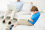 Sad little boy sitting on sofa with his father working on laptop in background