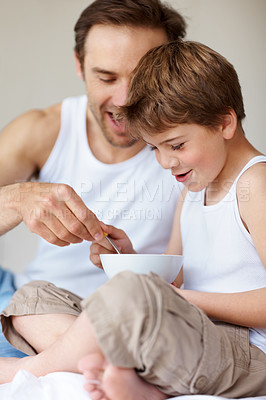 Buy stock photo Portrait of a happy young father and son eating a healthy breakfast together