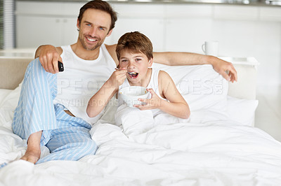 Buy stock photo Portrait of a happy young father and his son eating breakfast while watching  television on bed