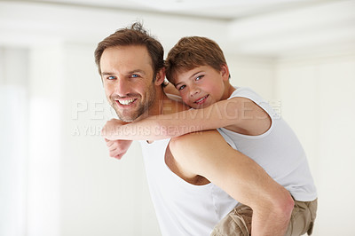 Buy stock photo Portrait of a happy young father smiling and giving his son piggiback ride