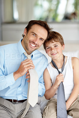 Buy stock photo Portrait of a happy young father and son showing their neckties and smiling - Family