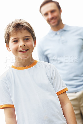 Buy stock photo Portrait of a cute young boy standing with his father in background