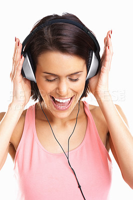 Buy stock photo Closeup of a happy young woman enjoying music while wearing headphones - isolated on white