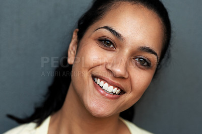 Buy stock photo Closeup portrait of a happy young Indian woman smiling against grey background
