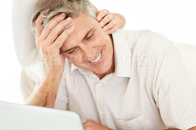 Buy stock photo Portrait of a smart mature man smiling white with a laptop and a hand of a woman on his neck