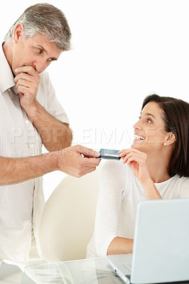 Buy stock photo Portrait of a mature man thinking before giving his credit card to wife for shopping online