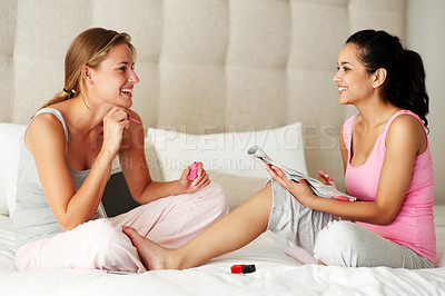 Buy stock photo Portrait of lovely young females applying nailpaints while sitting on the bed