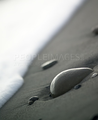 Buy stock photo Close up shot of a stone and some pebbles in the sand, by the seaside. The wash of a retreating wave is seen. Natural lighting.
