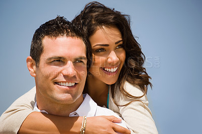 Buy stock photo Smiling young man giving piggyback to woman on holiday. Girl hugging her boyfriend