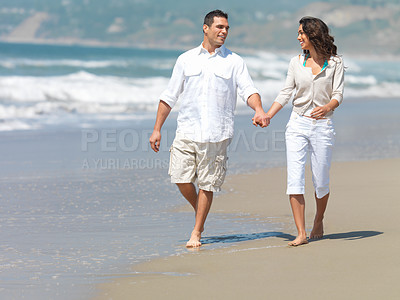 Buy stock photo Happy young couple holding hands on beach, walking along the water. Beautiful couple in love.