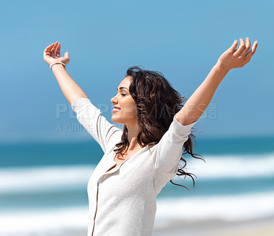 Buy stock photo Pretty young woman with her arms raised while standing on the beach