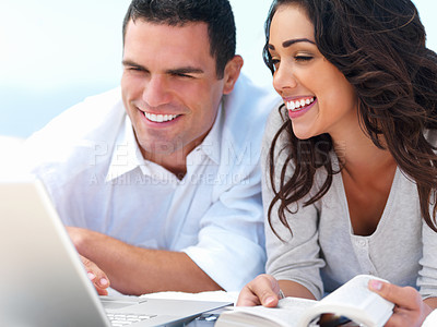 Buy stock photo Young smiling couple looking at laptop with book in hand