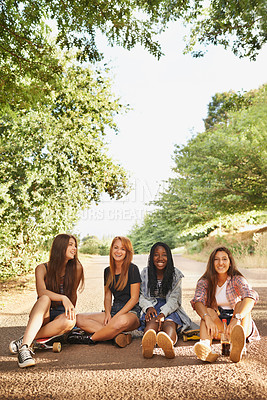 Buy stock photo A group of multiracial teens sitting outdoors enjoying each other's company