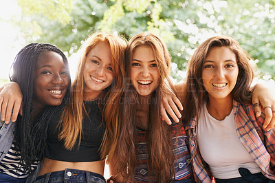 Buy stock photo Four pretty young girls holding each other while sitting outside