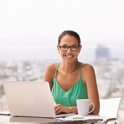 Buy stock photo A young woman sitting outdoors while working on her laptop