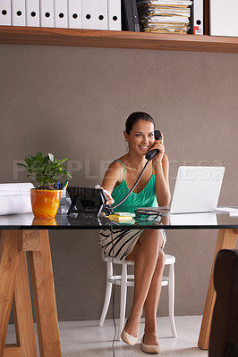 Buy stock photo A young businesswoman taking a phone call while working in her home office