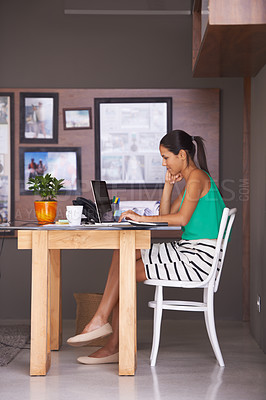 Buy stock photo A full length shot of a young woman sitting at her desk