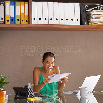 Buy stock photo Cropped shot of a young woman smiling happily while reading a document