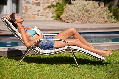 Buy stock photo Full length shot of a young woman relaxing with a book beside a swimming pool