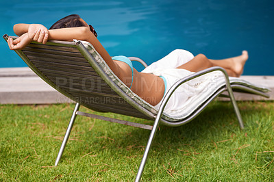 Buy stock photo Rear view of a beautiful young woman relaxing in a lounge chair by a swimming pool