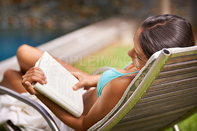 Buy stock photo A young woman reading a book while relaxing in a lounge chair by a swimming pool