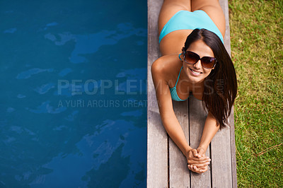 Buy stock photo Portrait of a beautiful young woman relaxing by a swimming pool