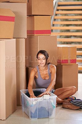 Buy stock photo Shot of a young woman moving into a new home