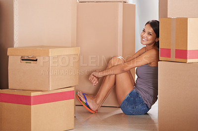 Buy stock photo A young woman sitting on the floor of her home among cardboard boxes