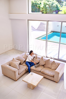 Buy stock photo Shot of a young woman relaxing on her sofa using a laptop