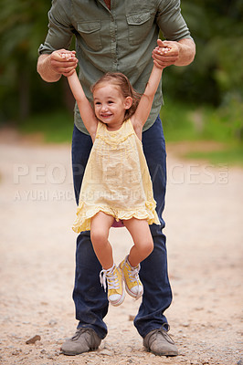 Buy stock photo A young girl being lifted up by her dad