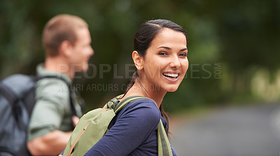Buy stock photo A beautiful woman smiles happily at the camera with her husband in the background