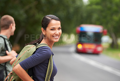 Buy stock photo A beautiful young woman wearing a backpack while waiting for a bus with her husband