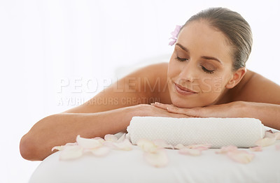 Buy stock photo Shot of a beautiful young woman lying on a massage table