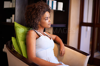 Buy stock photo Shot of an attractive african american woman sitting in a chair
