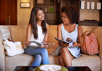Buy stock photo Shot of two friends sitting on a sofa reading through magazines