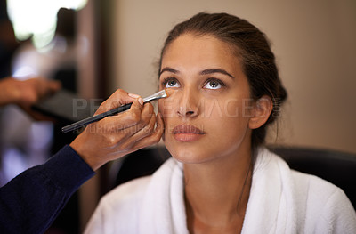 Buy stock photo Shot of an attractive young woman having makeup applied to her face