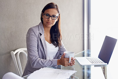 Buy stock photo An attractive young businesswoman having a coffee break at her office desk