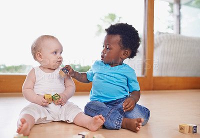 Buy stock photo A shot of two adorable babies playing with building blocks