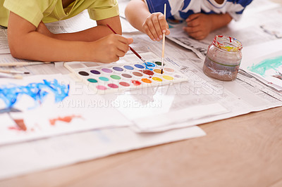 Buy stock photo Cropped shot of two young boys painting pictures at home
