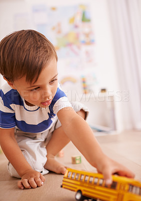 Buy stock photo Shot of a cute little boy playing with a yellow toy truck in his room