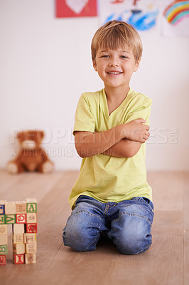 Buy stock photo A little boy sitting proudly next to a tower he built