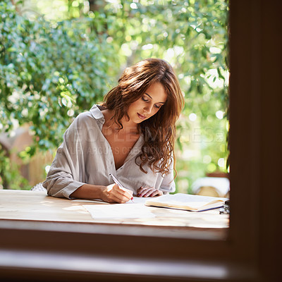 Buy stock photo Shot of an attractive young woman writing in a relaxed environment outdoors