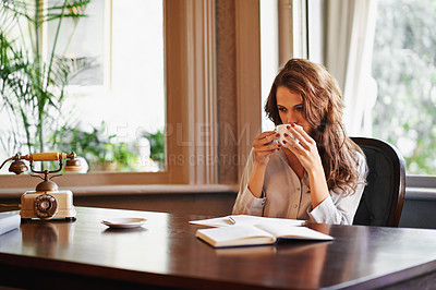 Buy stock photo Shot of an attractive young author enjoying a cup of coffee while writing indoors